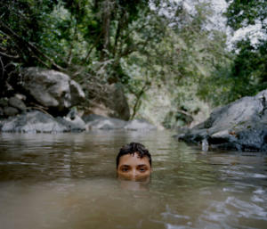 "Villalba, Puerto Rico, July 2018. ""My cousin Eliam cools off in a small pool of water after hiking down from our grandfather Horacio's home in the barrio of Dajaos. The barrio is named after the small fish that frequent the streams in the area."""